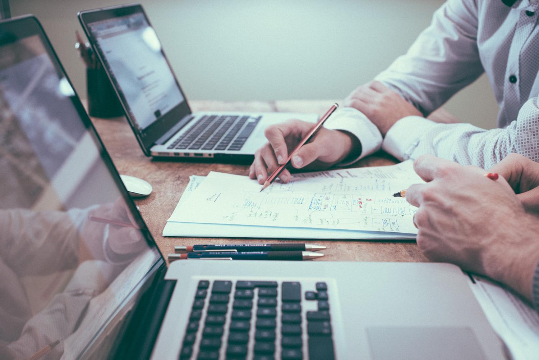 Menschen arbeiten gemeinsam an einem Dokument am Schreibtisch mit zwei Notebooks