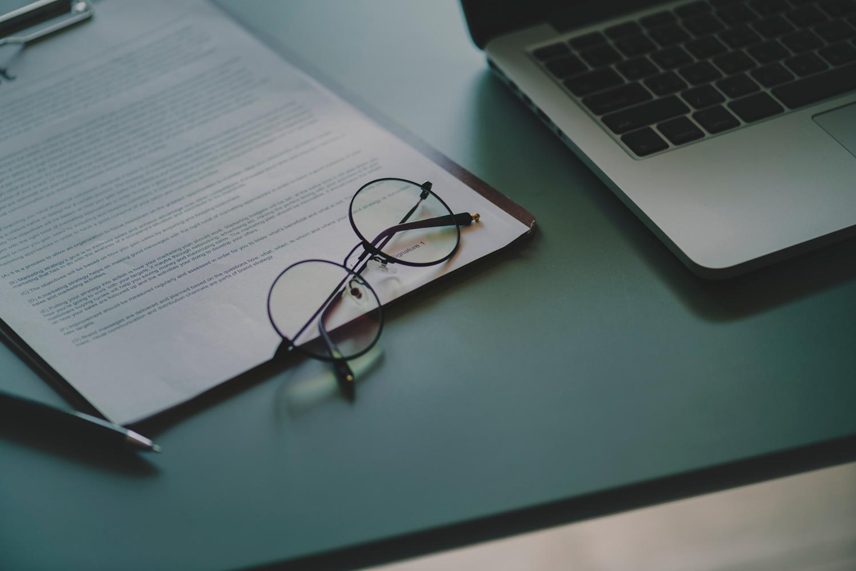 Brielle mit runden Gläsern auf Schreibtisch