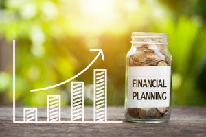 """Diagramm mit steigenden Umsätzen, daneben eine gefüllte Spardose mit der Banderole """"Financial Planning"""""""