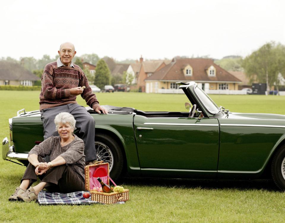 Ein älteres Ehepaar macht ein Picknick auf einer grünen Wiese neben Ihrem Oldtimer.
