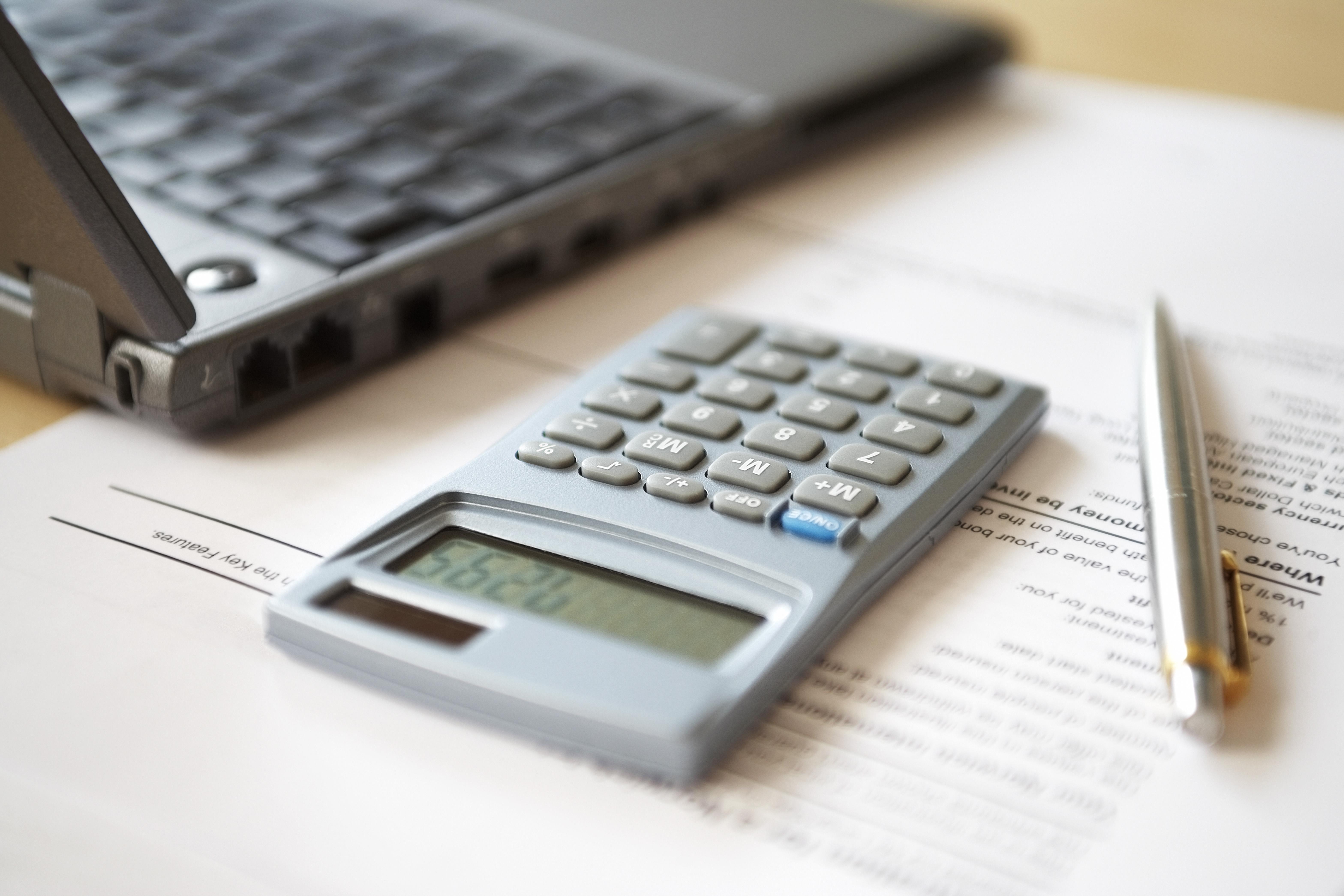 Bild von einem Notebook, einem Taschenrechner und einem Stift.