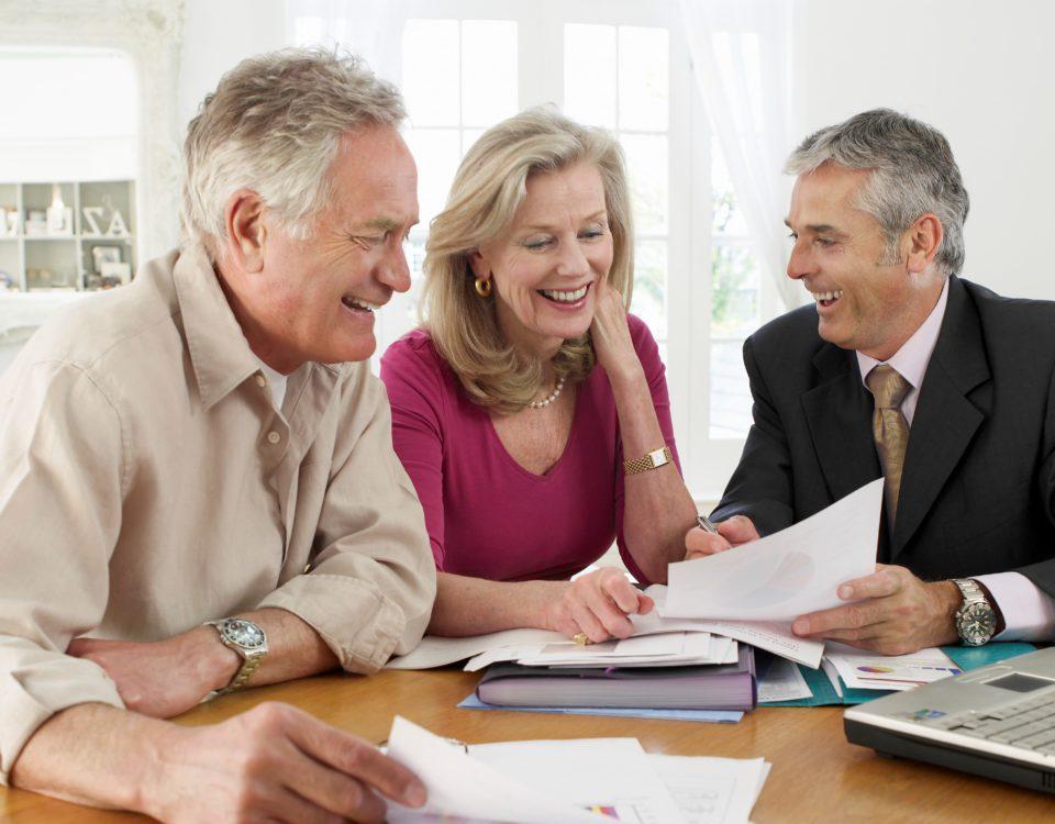 Ein Berater berät ein älteres Ehepaar am Esstisch Ihres Hauses.