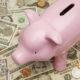 Ein Sparschwein steht auf Dollarscheinen.