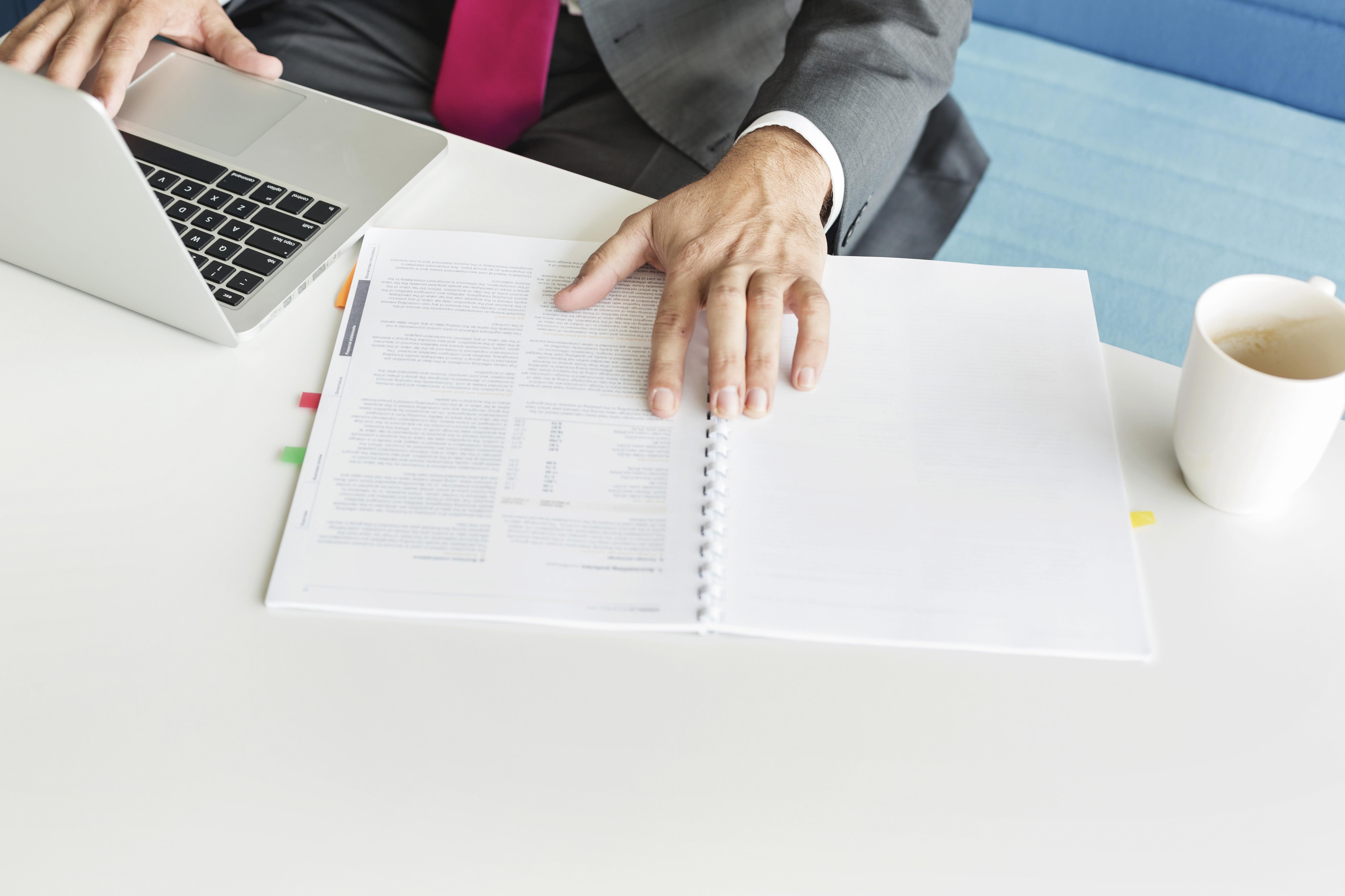 Eine Person arbeitet am Notebook, nebenher liest sie einen Bericht durch.