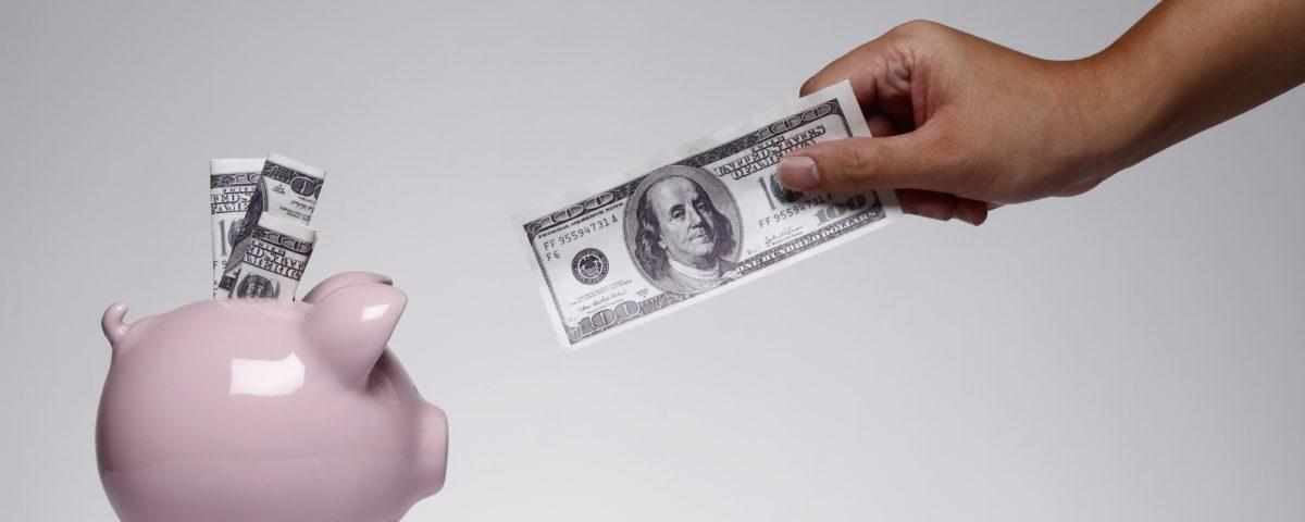 Eine Person möchte einen 100$-Schein in eine Sparschwein stecken.