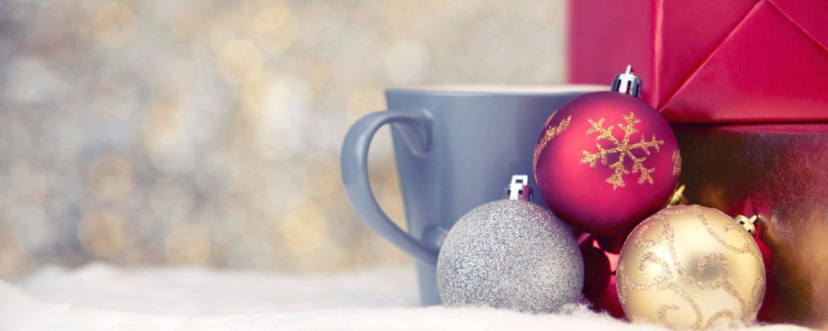 Ein weihnachtliches Bild mit einigen Christbaumkugeln, einer Tasse und zwei Geschenken.