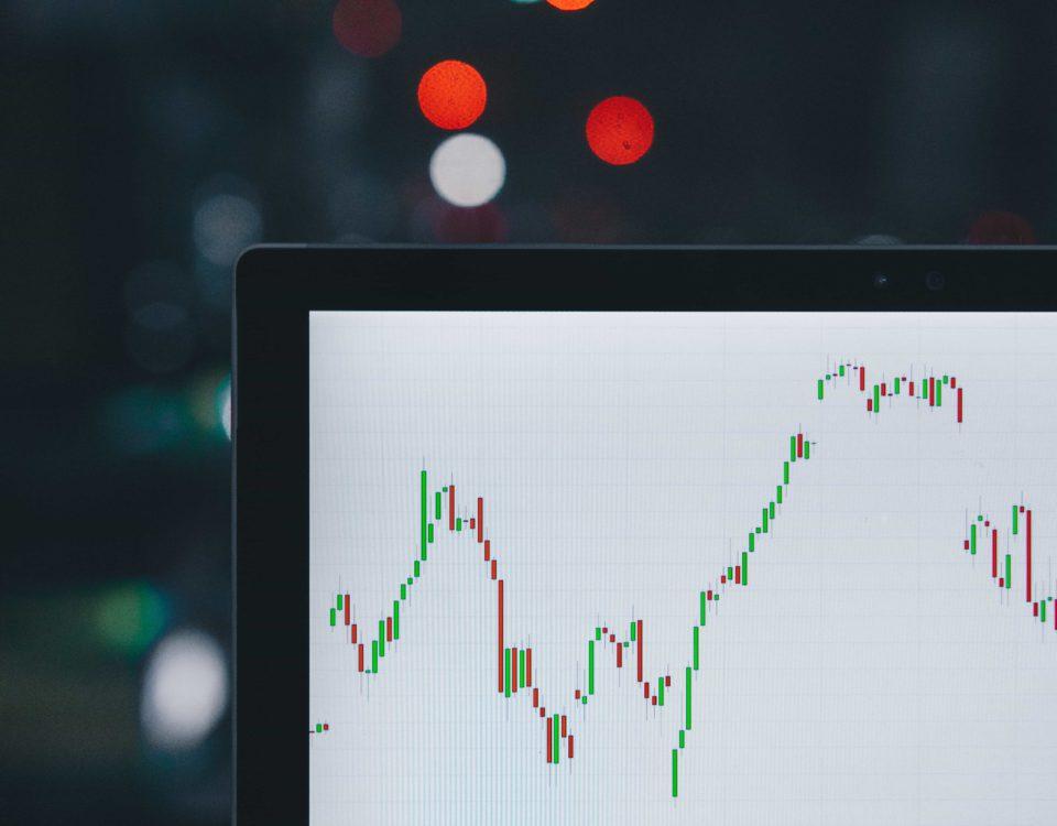 Laptop, der Aktienkurs mit Kerzen anzeigt