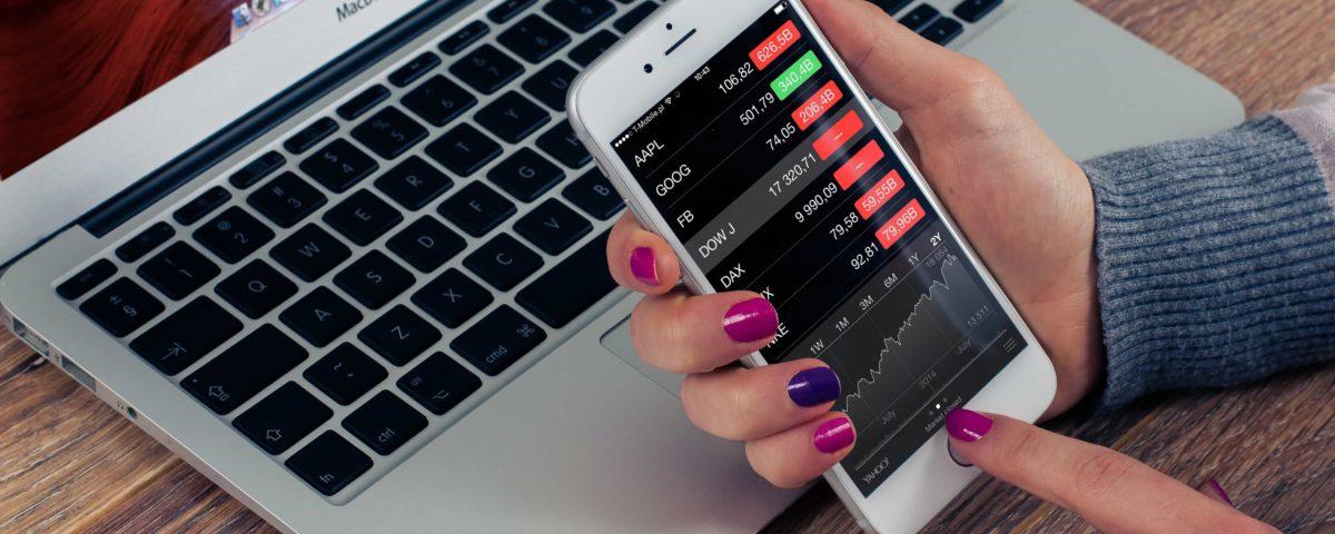 Frau hält Smartphone in der Hand und befindet sich in der Aktien App